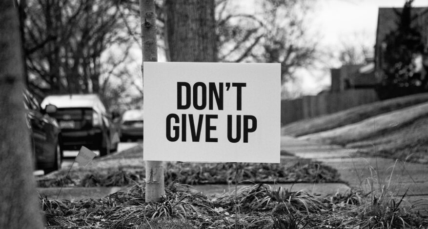 "Black and white picture of a sign that says ""DON'T GIVE UP"""