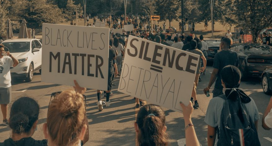 "Protestors holding signs saying ""Black Lives Matter"" and ""Silence = Betrayal"""